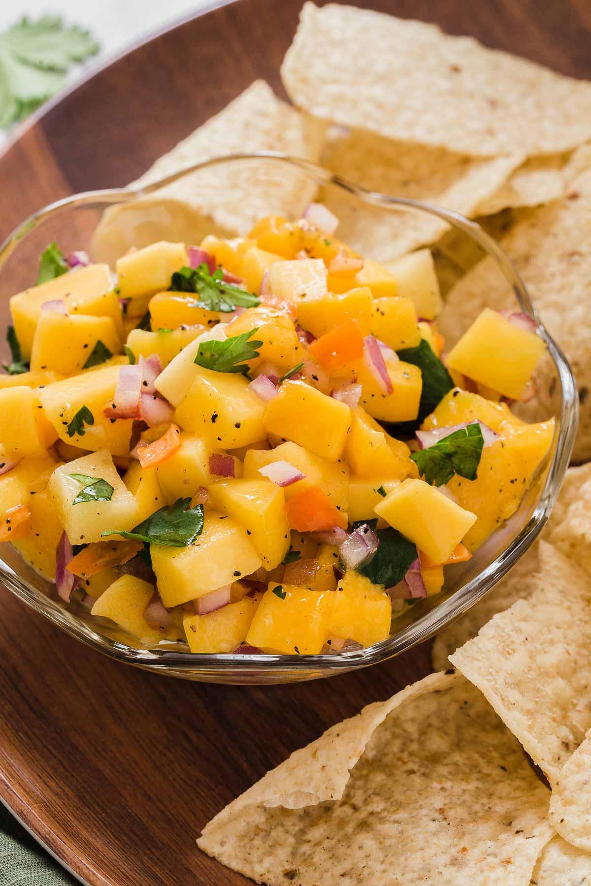 Bright orange mango habanero salsa in bowl with chips on side.