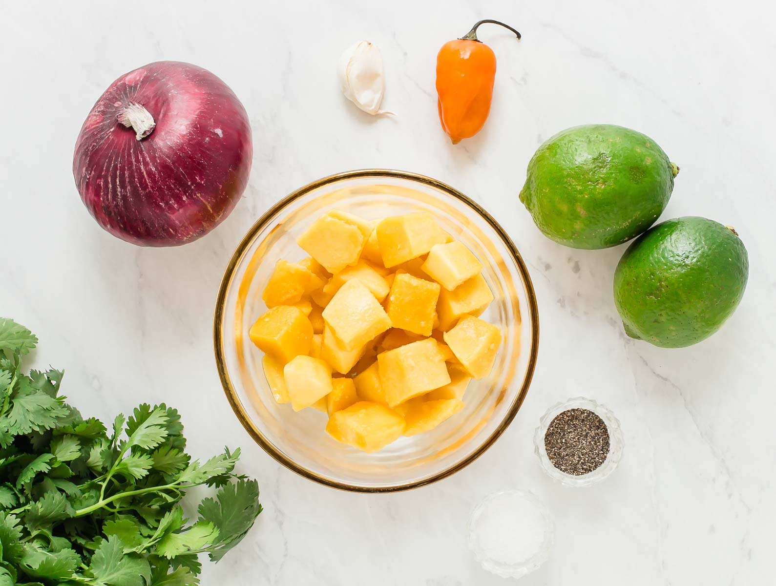 Ingredients for mango salsa on white table.