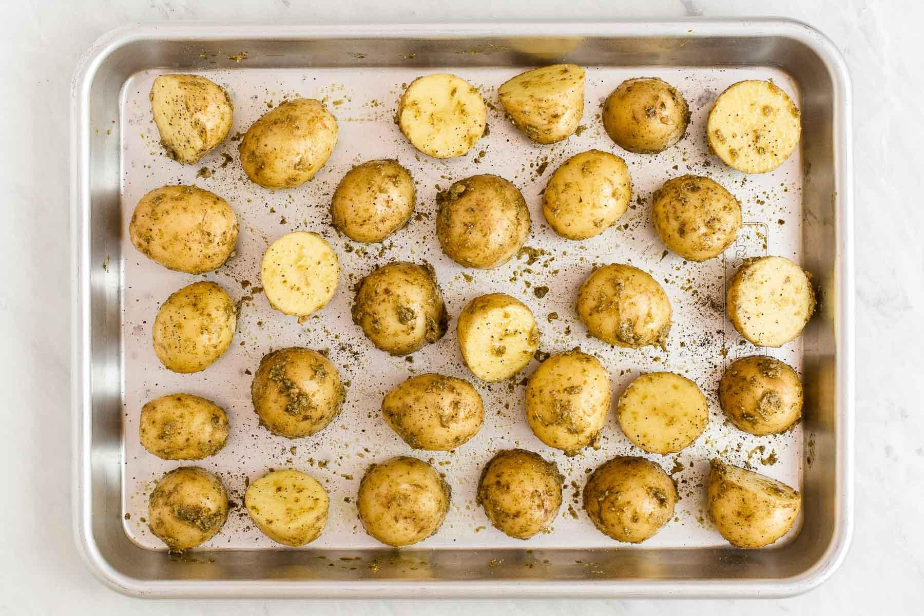 Raw potatoes on sheet pan with pesto coating.