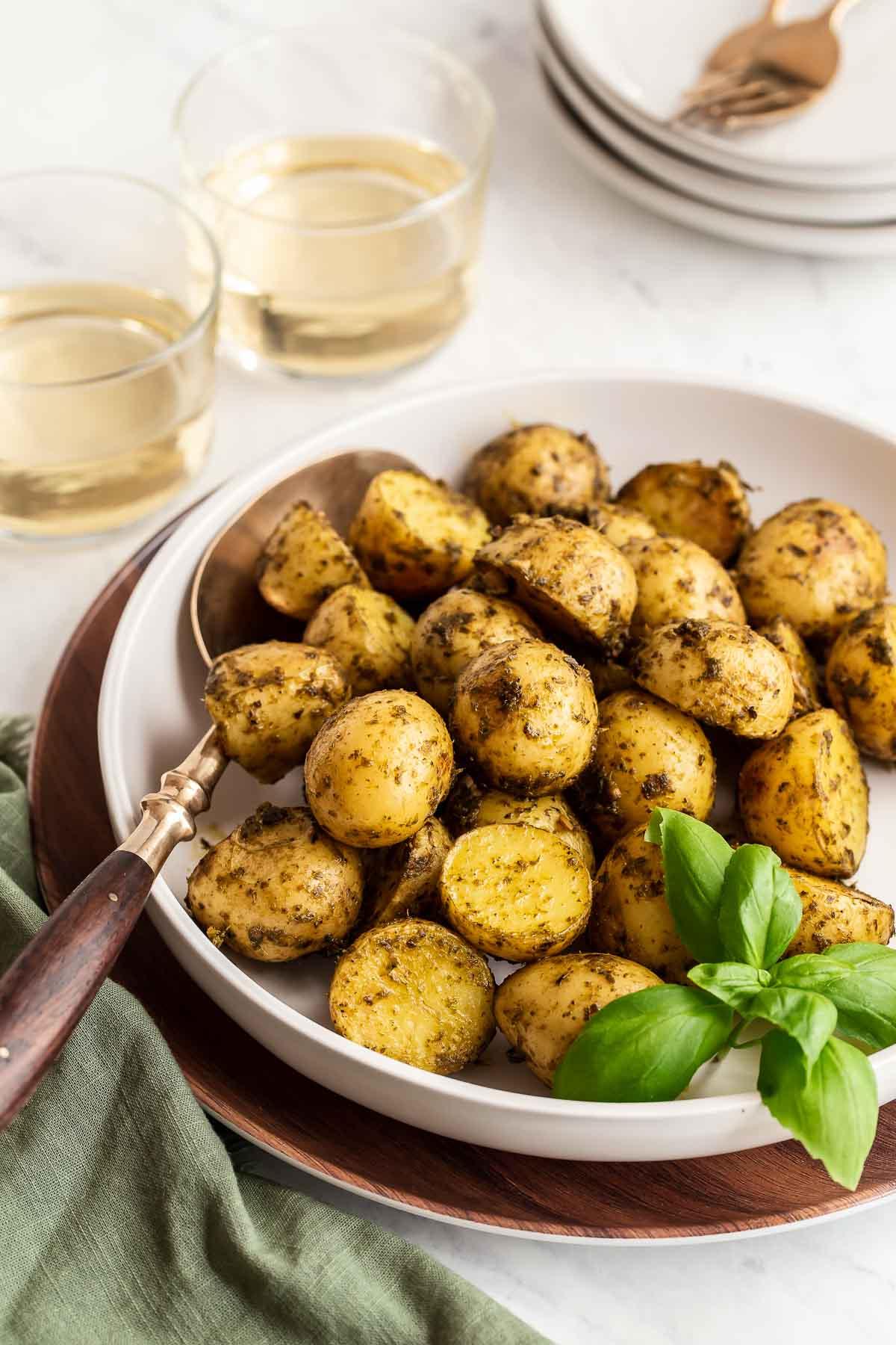 Pesto roasted potatoes in a white bowl.