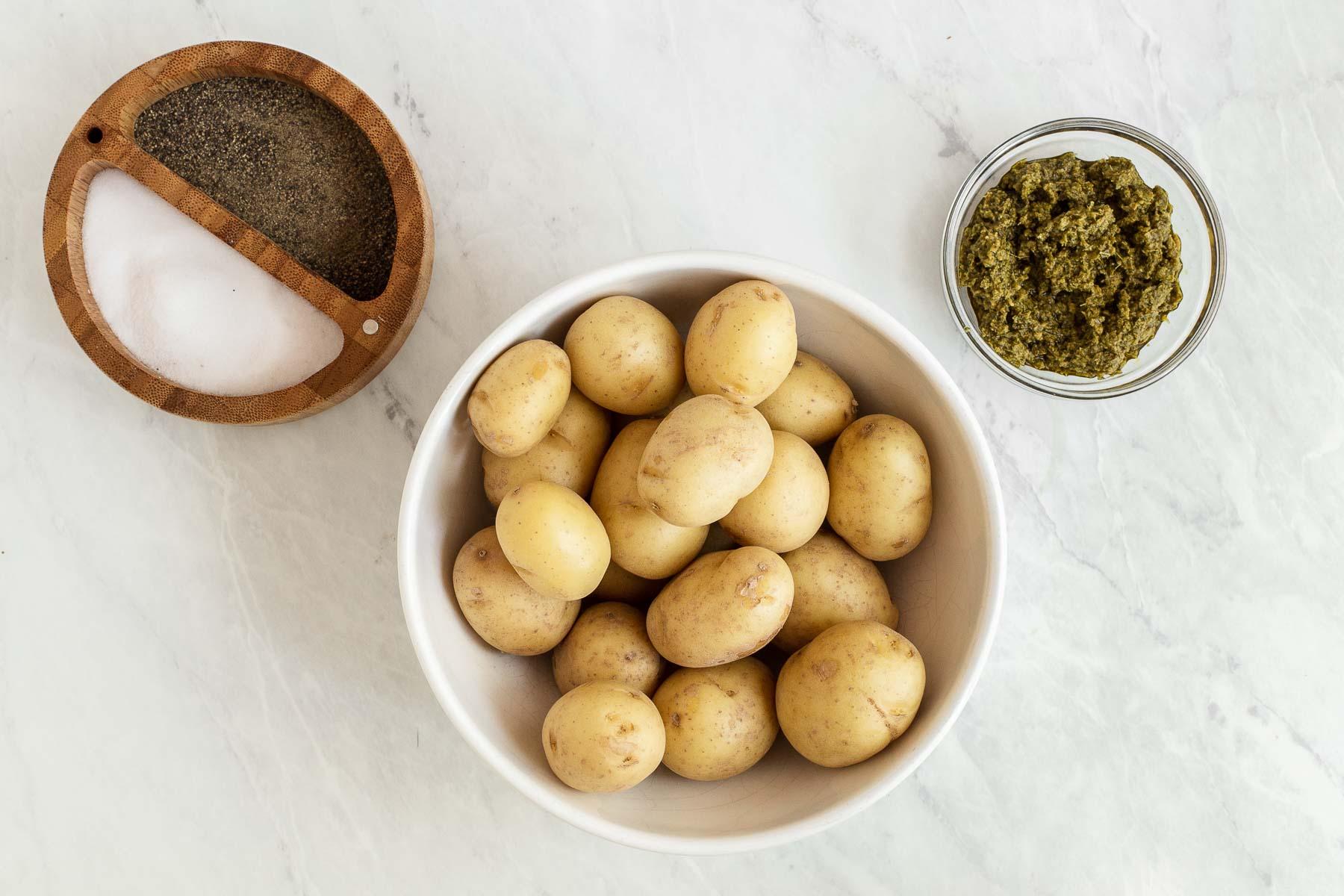 Ingredients to make pesto potatoes on white table.