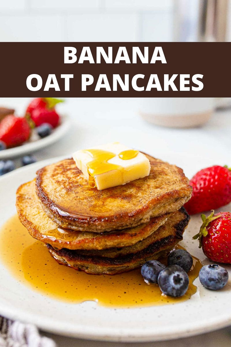 Stack of banana oatmeal pancakes on plate with fresh berries.