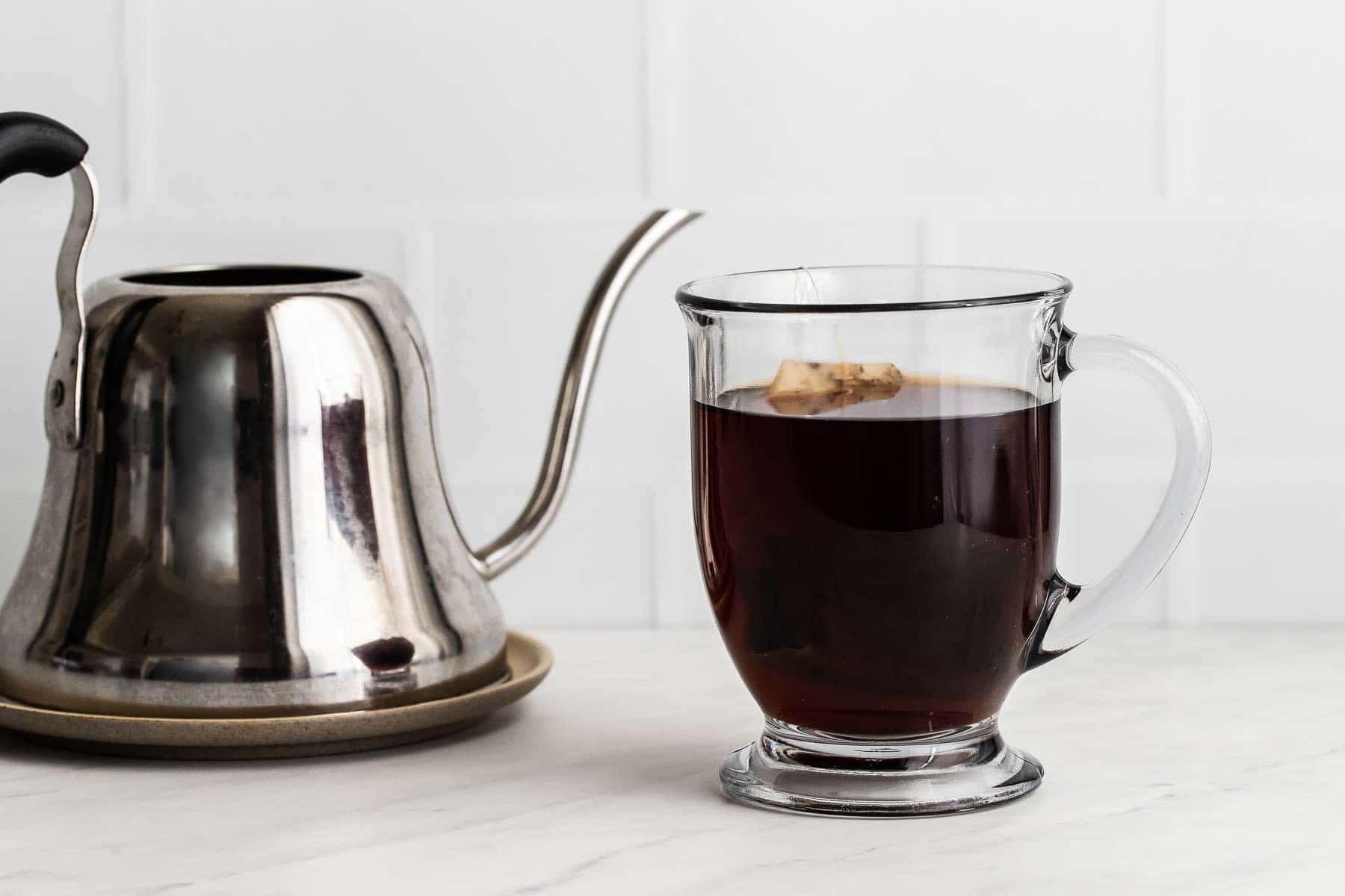 Earl Grey tea steeping in clear glass mug.