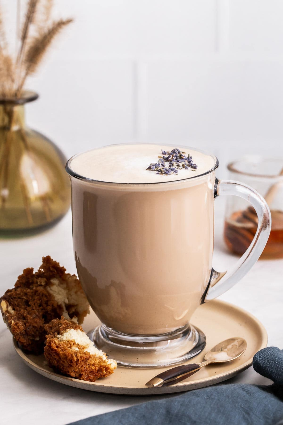 London fog tea latte in clear glass mug with lavender buds.
