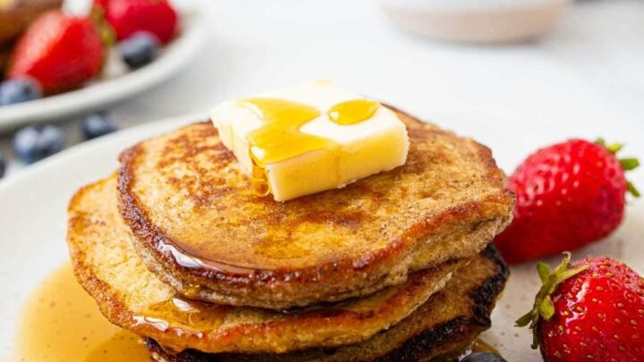Stack of banana oat pancakes with butter and maple syrup on top.