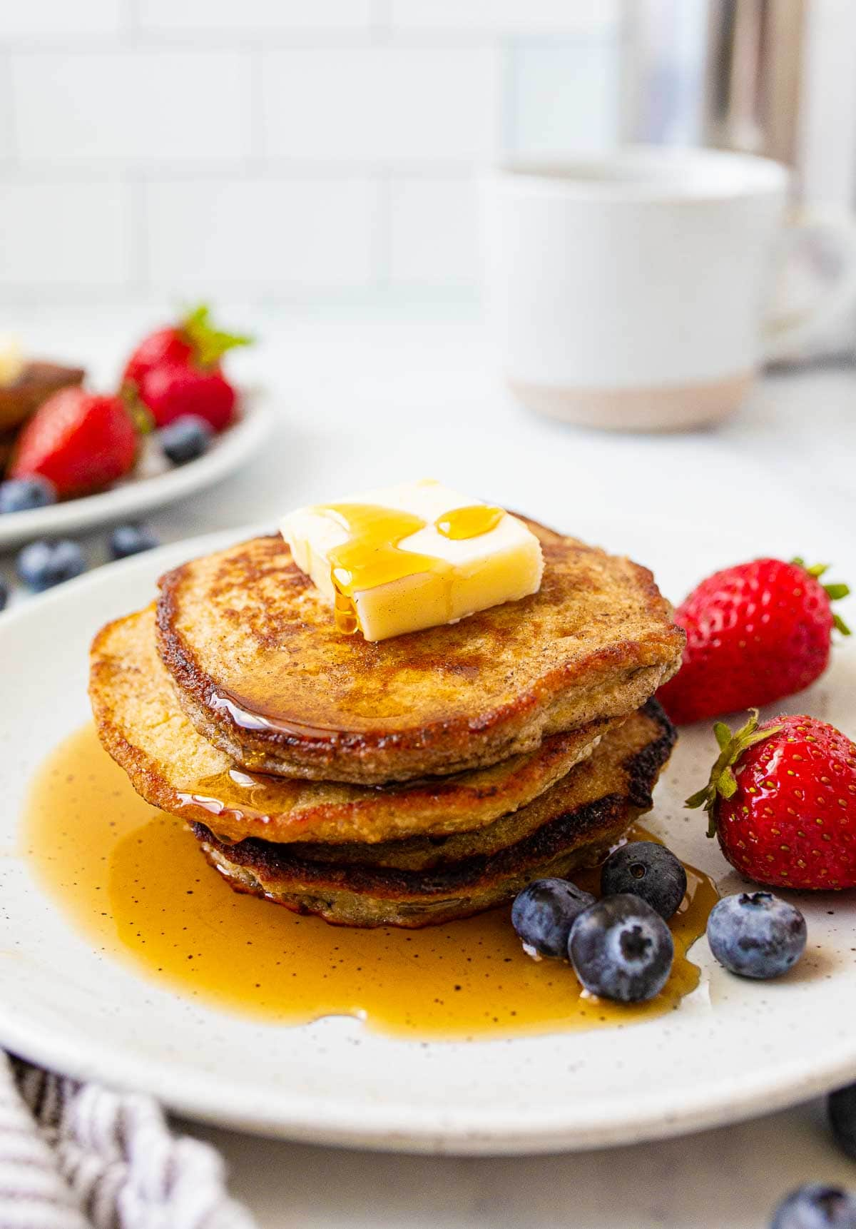 Stack of pancakes with butter and maple syrup on top.