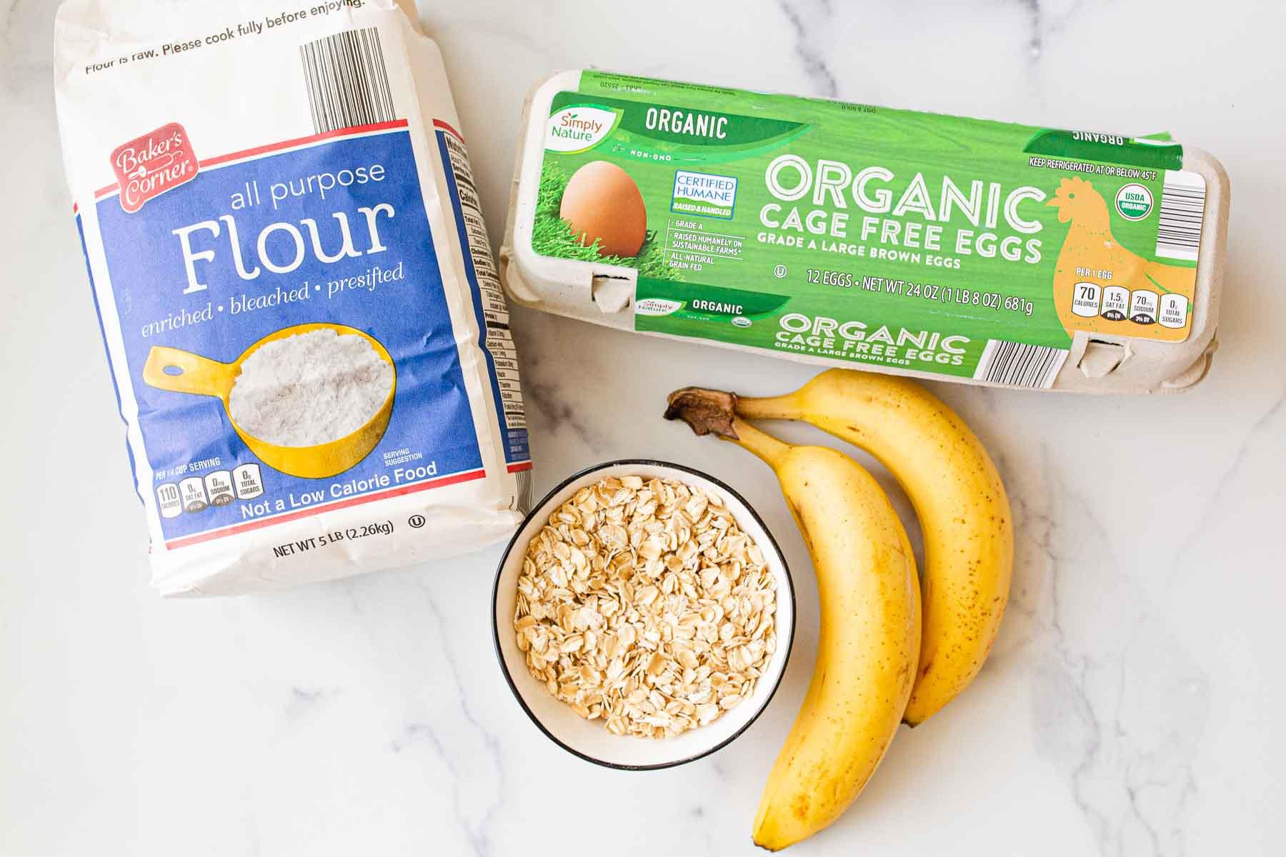 Flour, eggs, banana, and oats on white table.