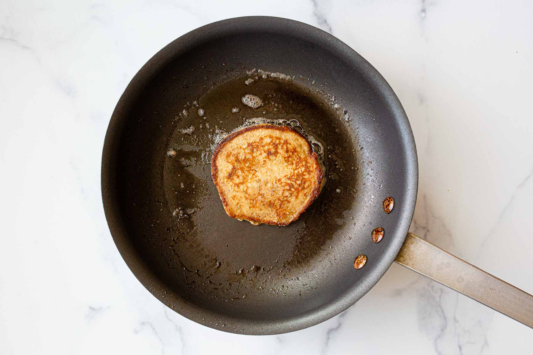 Cooked pancake in nonstick skillet.