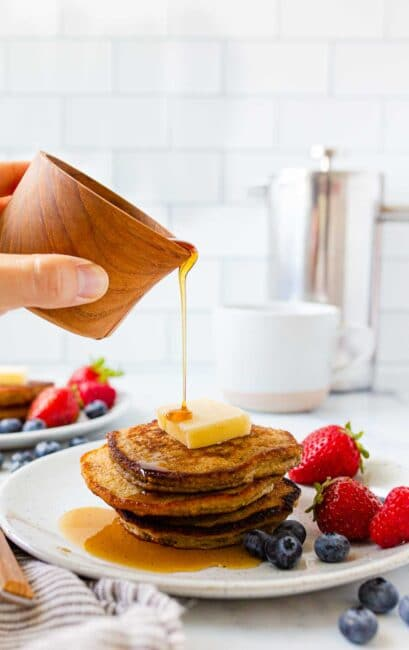 Syrup being poured on a pancake stack.