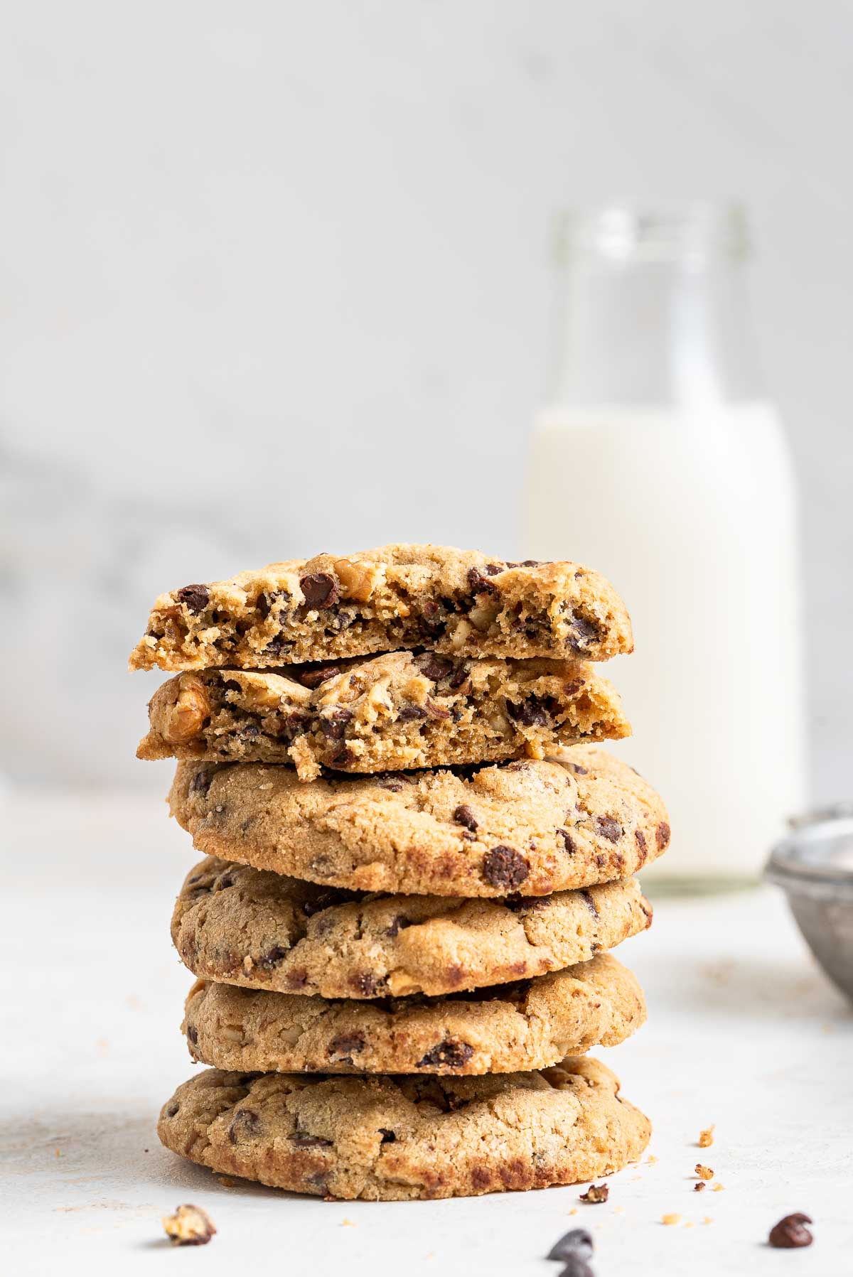 Stacked cookies with milk behind.