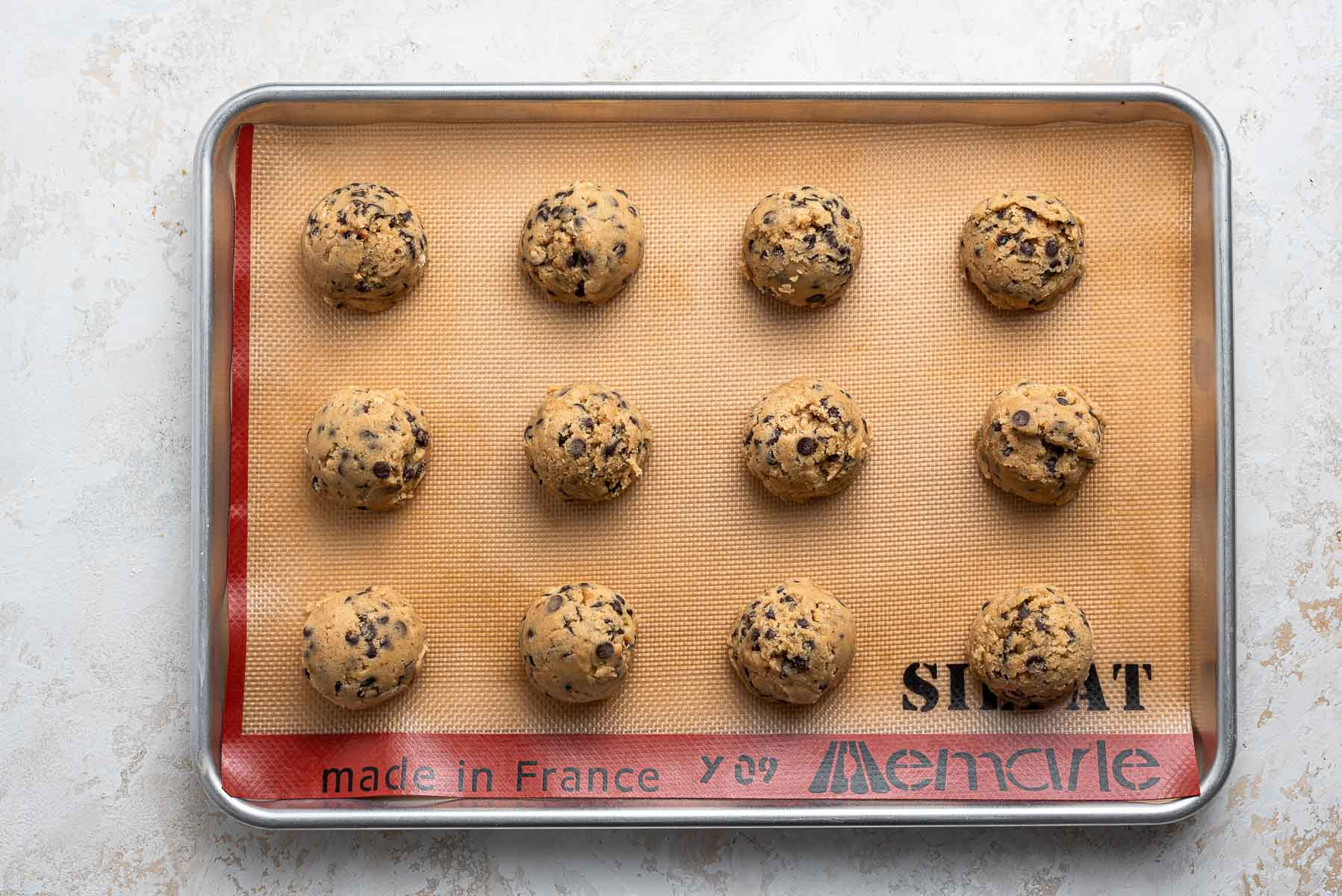 Raw cookie dough balls on baking sheet with silpat.