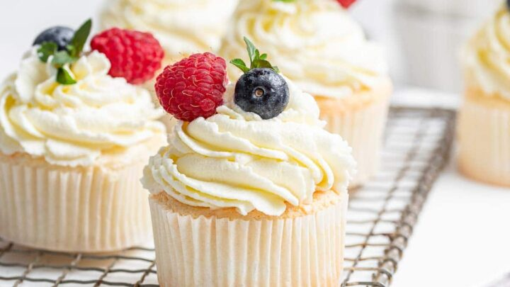 Four white angel food cupcakes on wire rack with fresh berries.