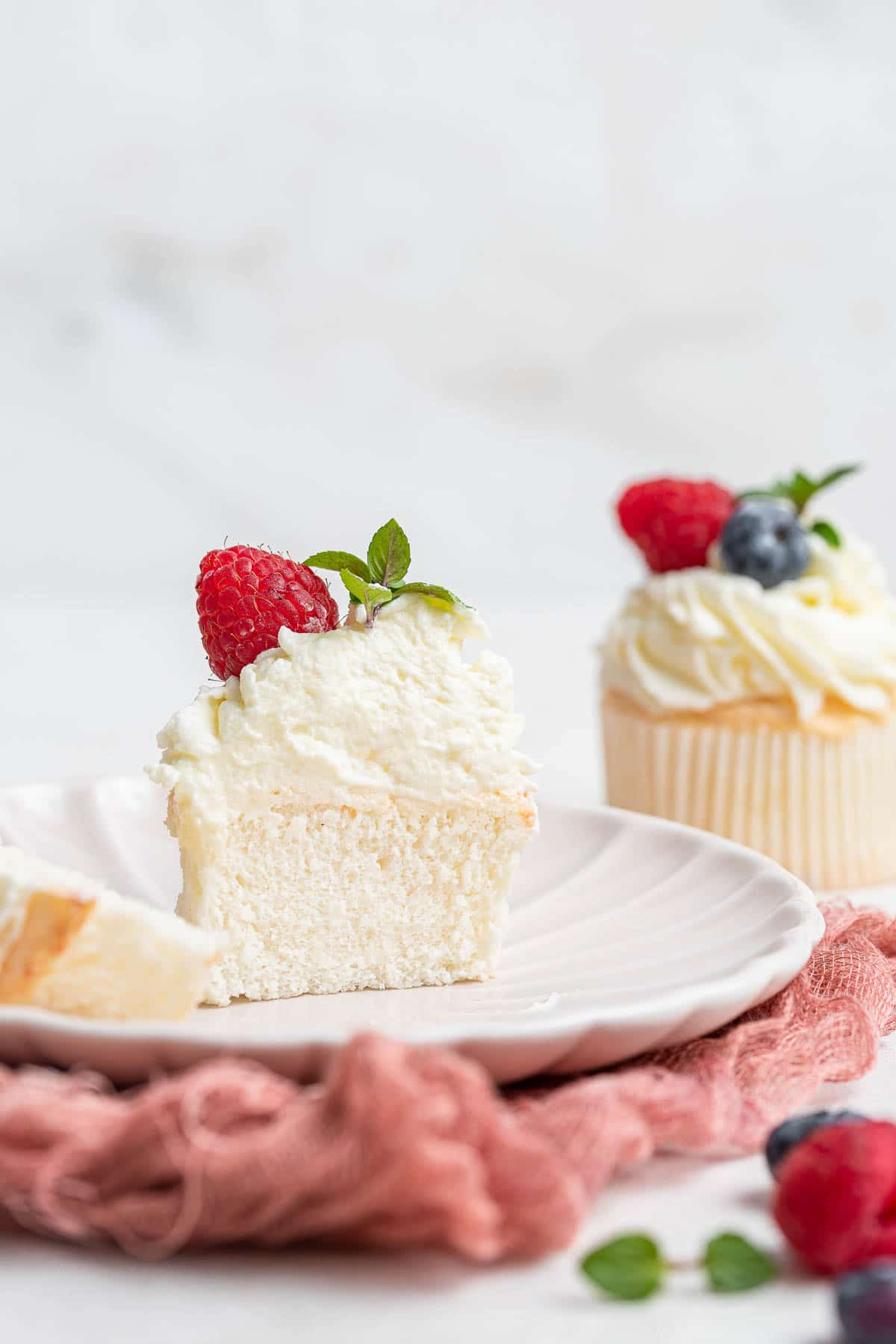 Angel food cake cupcake, sliced in half.
