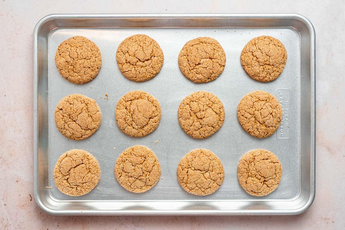 Baked crinkle cookies on a sheet pan.