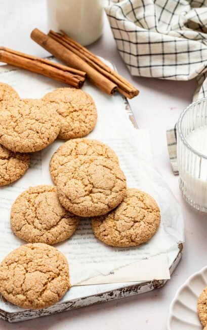Apple butter cookies on sheet pan with cinnamon sticks in background.