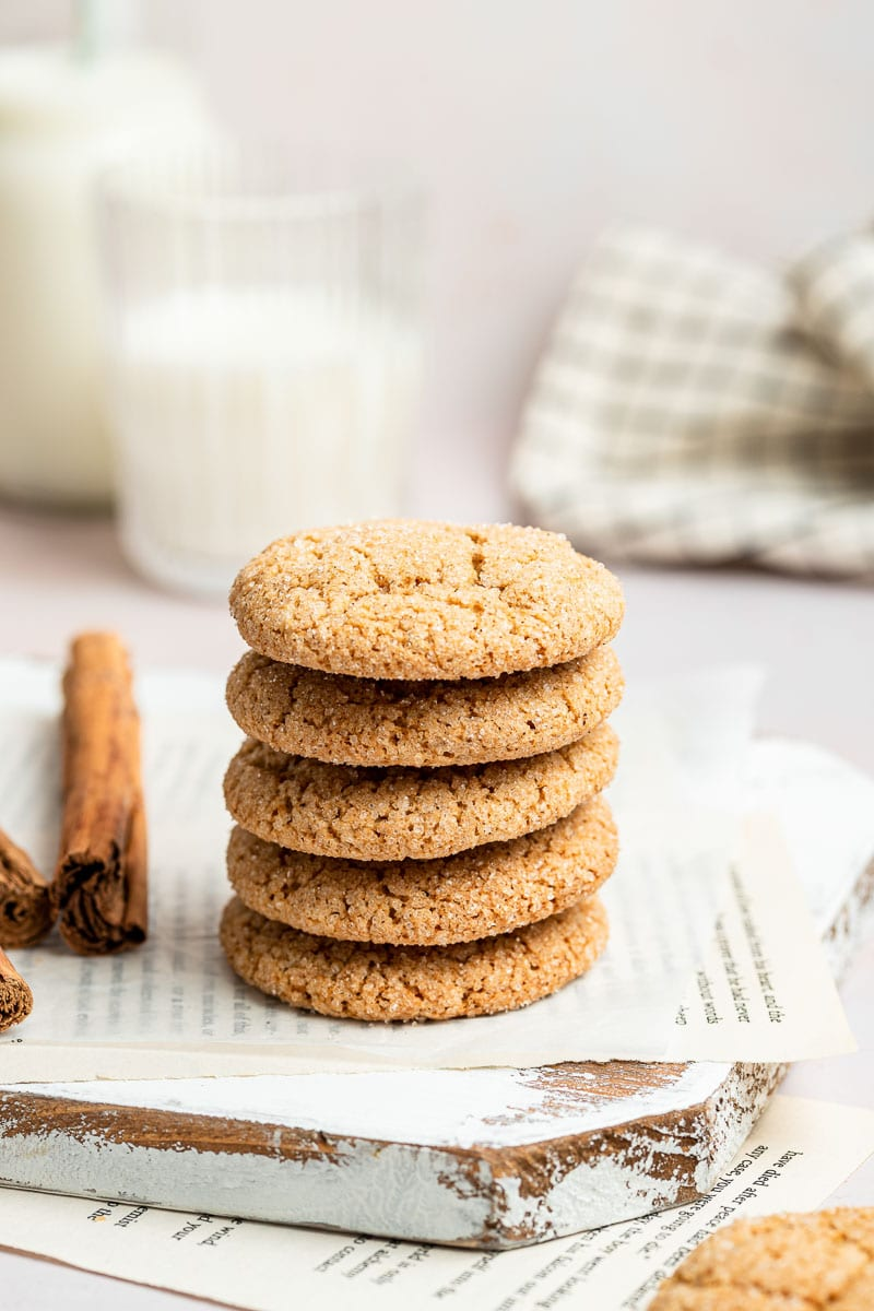 Stack of cookies next to glass of milk.